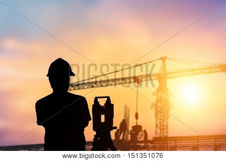 Silhouette engineer standing orders for construction crews to work safely on high ground over blurred natural background sunset pastel. heavy industry and safety at work concept.