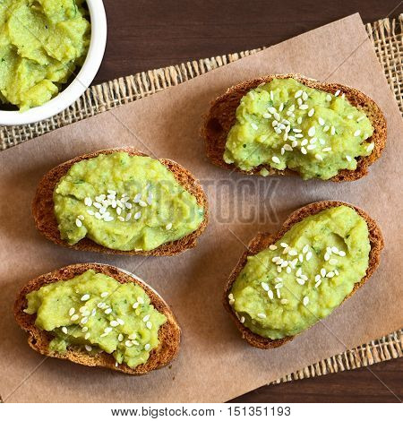 Toasted bread slices with green pea and parsley spread garnished with white sesame seeds photographed overhead with natural light (Selective Focus Focus on the top of the spread on the breads)