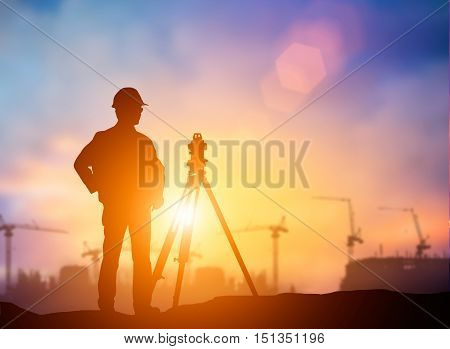 silhouette The young engineer working construction standards in line with global construction environment and the environment around the work site. over Blurred construction worker on construction site