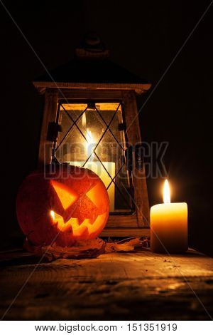 Halloween pumpkin and lantern with candle on black background