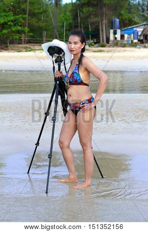 Women bikini sexy relax with camera on Thung Wua Lan Beach at Chumphon Province Thailand.