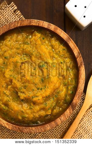 Pumpkin and parsley puree in wooden bowl photographed overhead on dark wood with natural light (Selective Focus Focus on the middle of the puree)