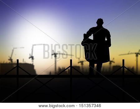 silhouette of engineer looking at blueprints on scaffold in a building site over Blurred construction site