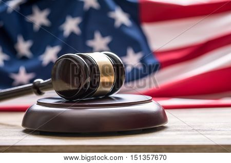 Judges wooden gavel with USA flag in the background. Symbol for jurisdiction.