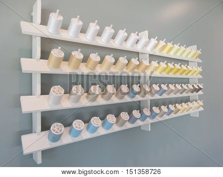 Skew view of multicolor bobbin storage on grey wall