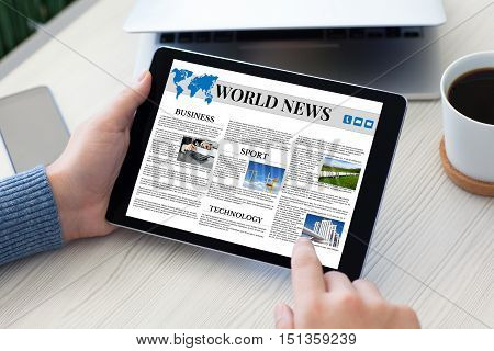 male hands holding tablet computer with world news over table notebook and phone