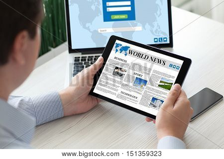 man holding tablet computer with world news over table with notebook phone