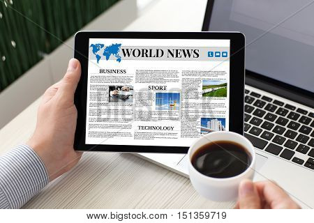 man holding tablet computer with world news on screen and coffee near notebook