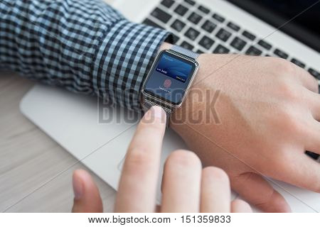 smart watch in man hand with debit card touch and pay near notebook