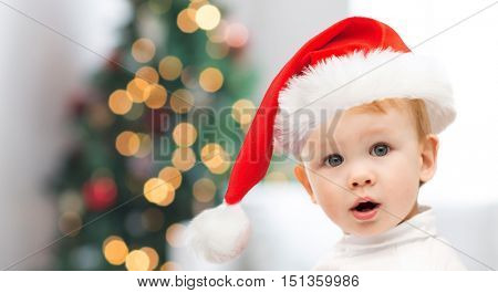 childhood, holidays and people concept - beautiful little baby boy in christmas santa hat over christmas tree lights background