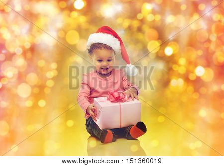 childhood, christmas, holidays and people concept - happy smiling little african american baby girl in santa hat with gift box sitting on floor over lights background
