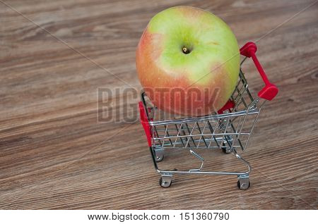 Big apple laying in shopping cart. Wooden background. Space for text
