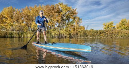 Senior male paddler enjoys workout on his racing stand up paddleboard on a lake in fall colors in northern Colorado