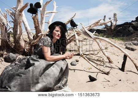 woman in a black gown comunicating with crows in desert