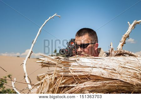Tactical special ops sniper behind cover of a tree stump in desert terrain