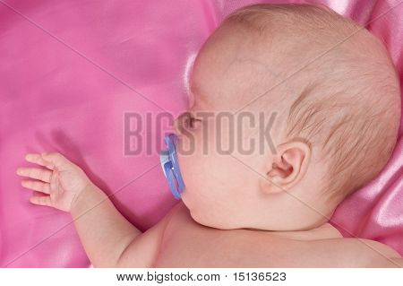 A Sweet Baby Sleeping On A Pink Sheet