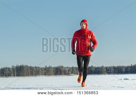Ultra trail runner wearing red protective sportswear on winter training session outdoors