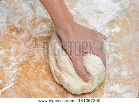 Woman's hand knead dough on the desk