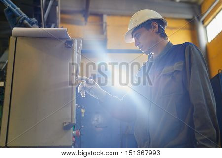 Male worker in overalls and helmet presses on the touch screen control panel equipment in the factory