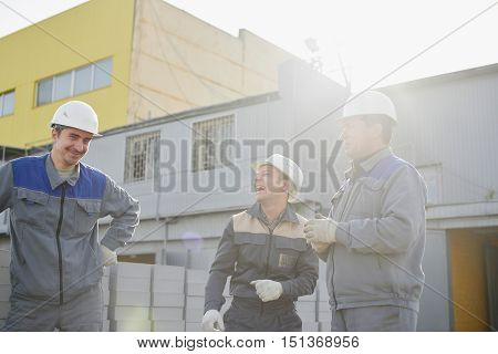 A group of construction workers in overalls and helmets on the background industrial building