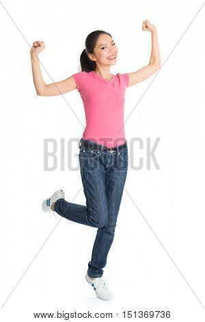 Portrait of excited young Asian woman in pink shirt and jeans arms raised celebrating success, full body standing isolated on white background.