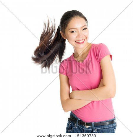 Portrait of happy young Asian woman in pink shirt and jeans with flying ponytail hair, standing isolated on white background.
