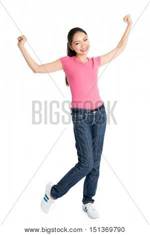 Portrait of excited young Asian girl in pink shirt and jeans arms raised celebrating success, full body standing isolated on white background.