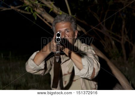 Night poacher. Man in camouflage clothes ready to hunt with hunting rifle