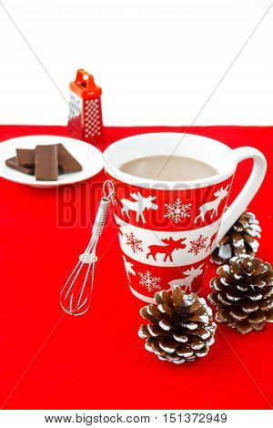 Hot Chocolate in a festive mug with winter motives a small whisk chocolate and chocolate grater on red place mat surrounded by snowy pine cones.