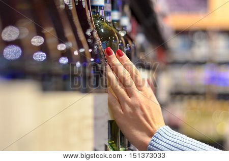 Woman Choosing A Bottle Of Wine Off The Shelf