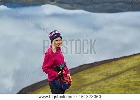 woman hiker photographer taking picture on the lake background in Iceland