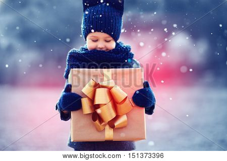 Adorable Kid With Big Gift Box Under A Snowfall. Focus On Gift Box