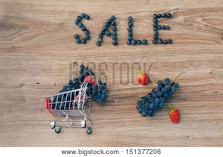 Small shopping cart with bunch of blue grapes inside word sale percent sign made of grapes and red strawberries on brown wooden table. Top view