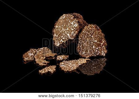 Black truffles mushrooms on black background, studio shot