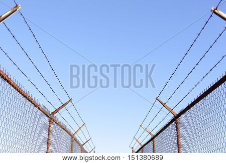 The pedestrian walkway between industrial sites protected by high wired fence (Seattle Washington).