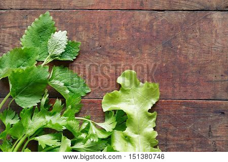 Bundle of freshness green parsley and salad leaves on wooden background