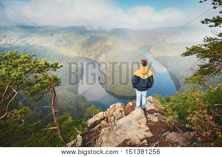 Traveler on the top of rock. Young man enjoying view on river valley in morning fog. Vltava river in Central Bohemia Czech Republic.