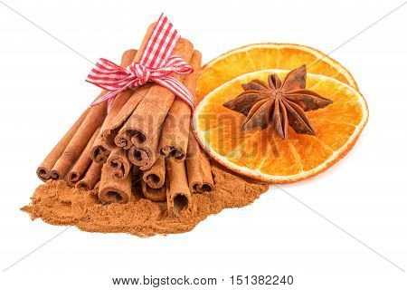 Bundle of cinnamon sticks with dried orange isolated on white. Traditional Christmas spices.