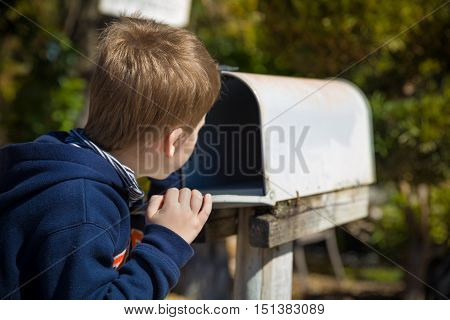 School boy opening a post box and checking mail. Kid waiting for a letter checking correspondence and looking into the in the metal mailbox.