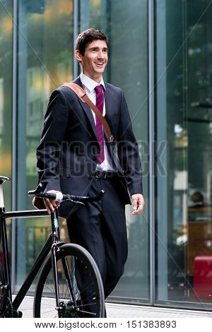 Businessman walking through town wheeling his bicycle along a pedestrian walkway past a commercial building with a smile on his face