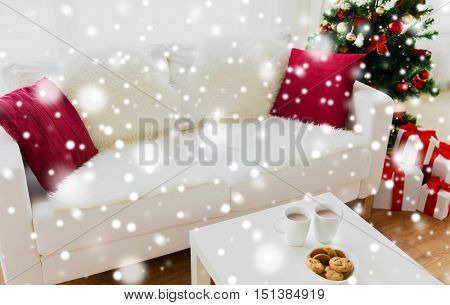 christmas, holidays, winter, celebration and still life concept - close up of cookies and cups with hot chocolate or cocoa drink on table at home