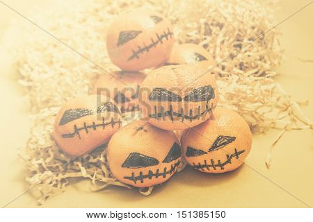 High key autumn background of angry orange mandarins dressed as frightening pumpkins. Spooky halloween oranges