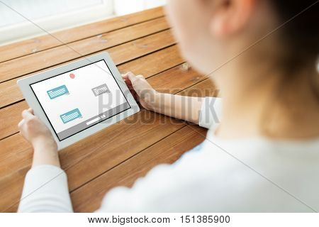 technology, people and online communication concept - close up of woman with messenger or internet chat on tablet pc computer screen on wooden table