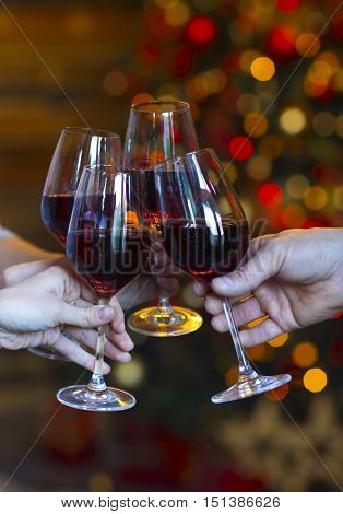 Clinking glasses of wine in hands on bright christmass tree lights background. Event celebration