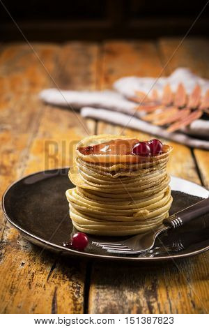 Pancakes with cranberry jam on a plate on warm color shabby wooden background. Autumn breakfast. Selective focus