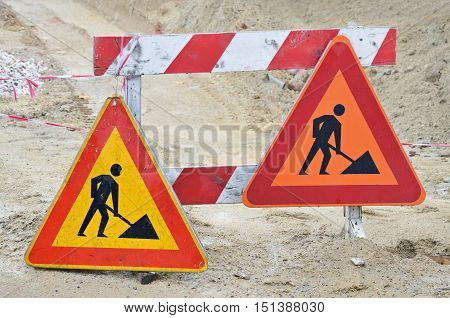 Two triangular warning signs on the road during the reconstruction