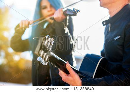 Buskers with girl violinist and man guitarist on blue sky outdoor. Music in sun rays.