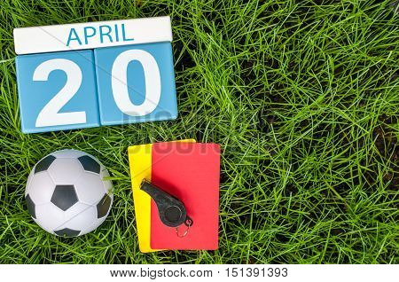 April 20th. Day 20 of month, calendar on football green grass background. Spring time, empty space for text.