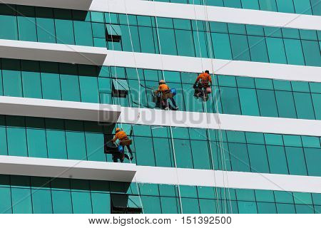 Worker Cleaning High Tower In Big City