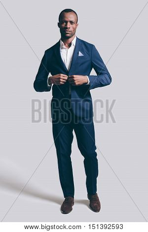 Looking just perfect. Full length of handsome young African man in full suit buttoning his jacket and looking at camera while standing against grey background